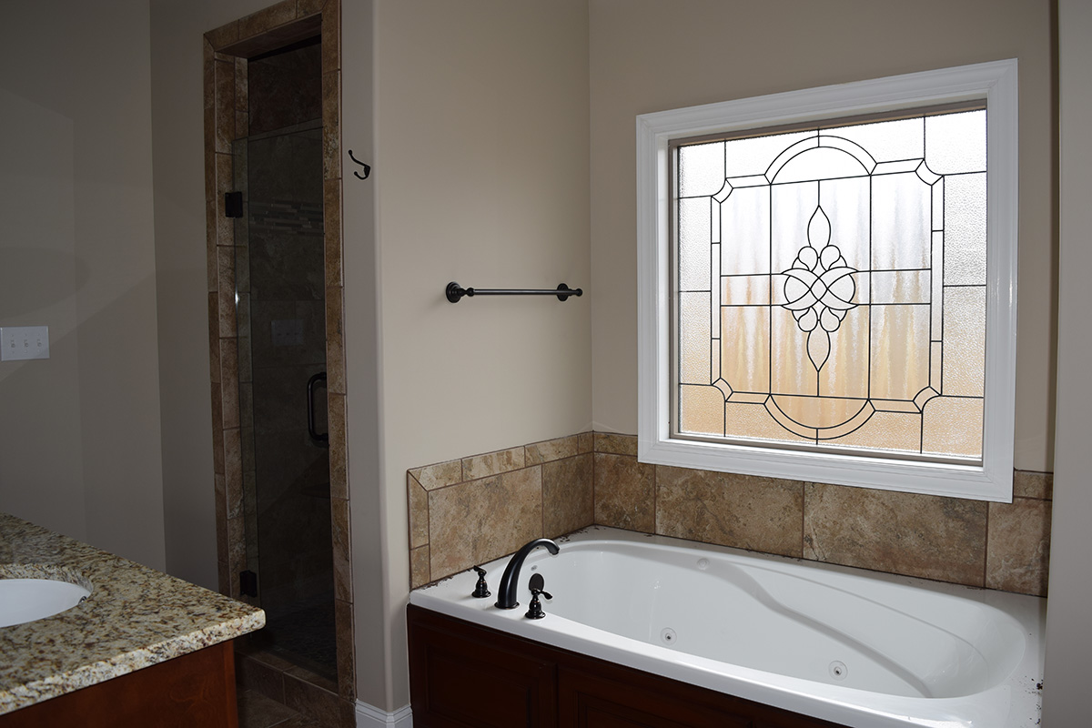 Hill Construction master bathroom with soaking tub and stained glass window