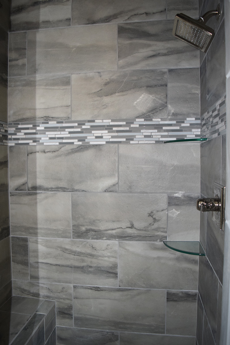 Hill Construction based in Decatur, AL gray tiled shower stall with rain shower head.