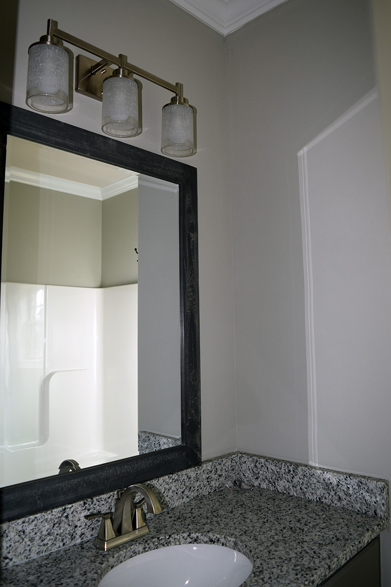 Hill Construction based in Decatur, AL wooden guest bathroom sink with granite countertops.