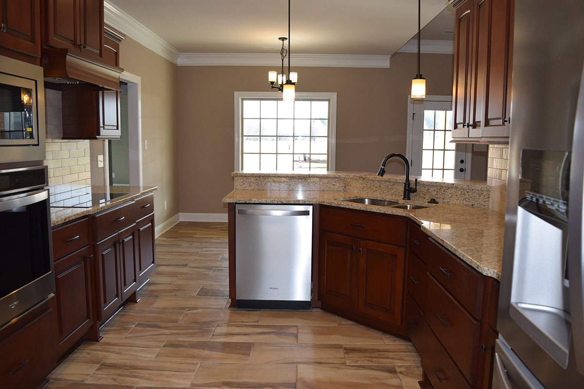 Hill Construction based in Decatur, AL kitchen with granite countertops and tiled flooring.