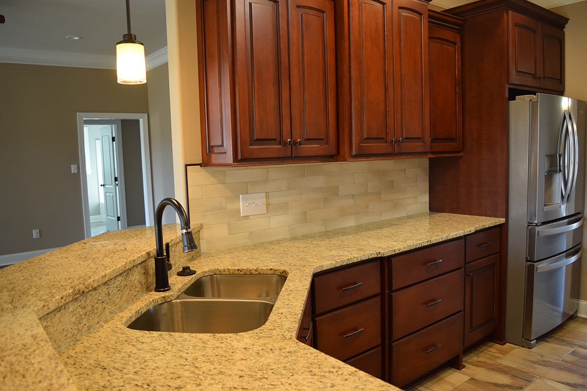Hill Construction based in Decatur, AL kitchen sink with raised granite countertop bar.