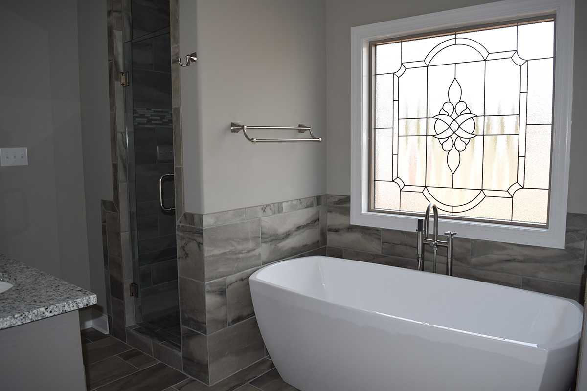 Hill Construction based in Decatur, AL bathroom soaking tub with stained glass window.